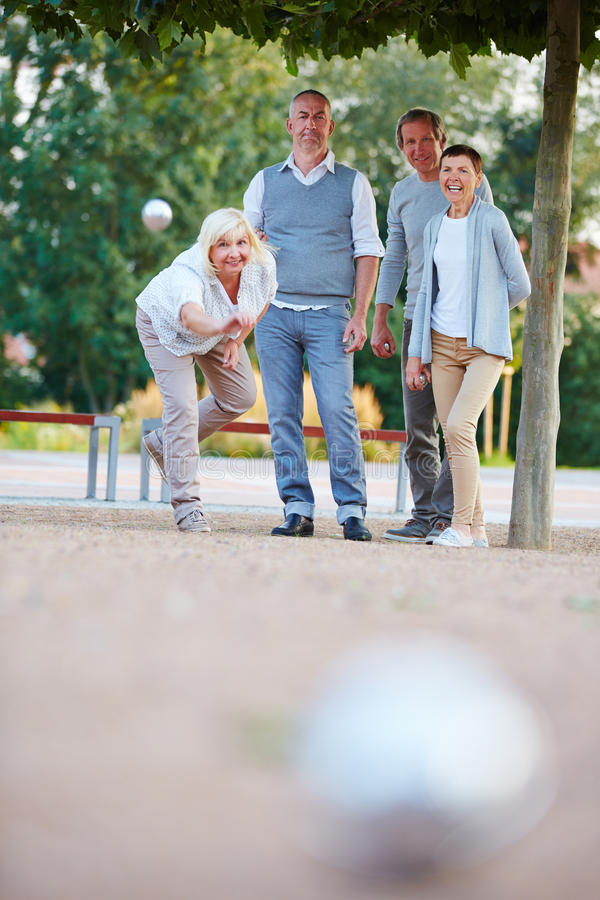 Woman throwing ball while playing boule stock images