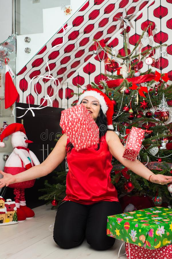 Woman throwing Christmas gifts. Cheerful woman throwing Christmas boxes gifts in front of tree in her house royalty free stock image