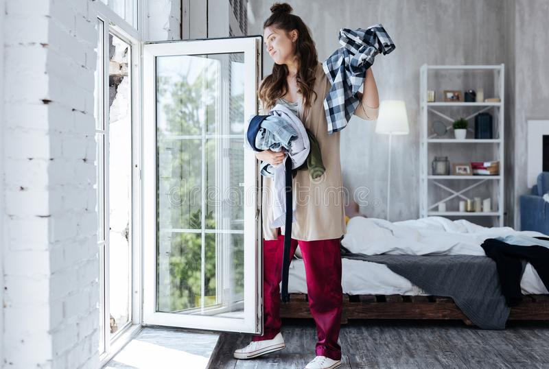 Woman throwing clothes of her ex husband from the window. Clothes away. Dark-haired woman wearing baggy clothes throwing clothes of her ex husband from the stock images