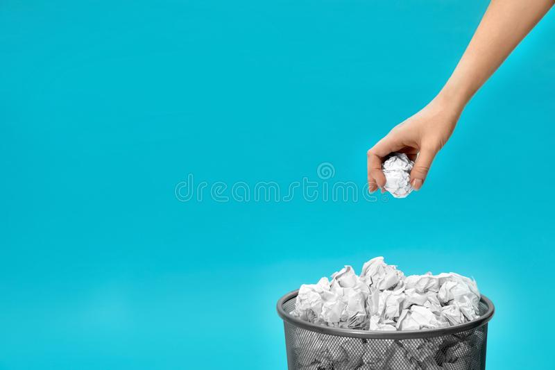 Woman throwing crumpled paper into metal bin on color background, closeup. Space for text stock image