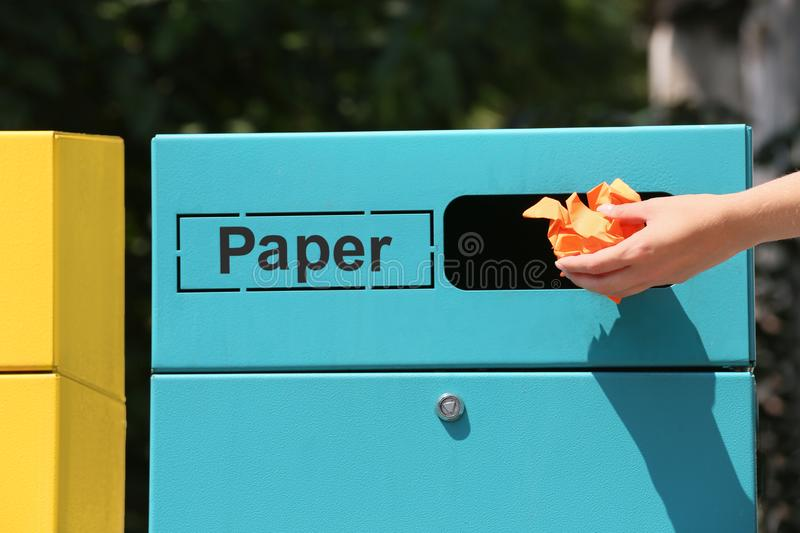 Woman throwing crumpled paper into sorting bin on city street, closeup. Recycling. Waste royalty free stock images