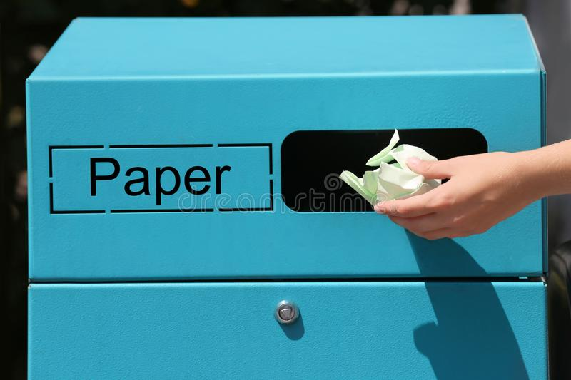Woman throwing crumpled paper into sorting bin on city street, closeup. Recycling waste stock image