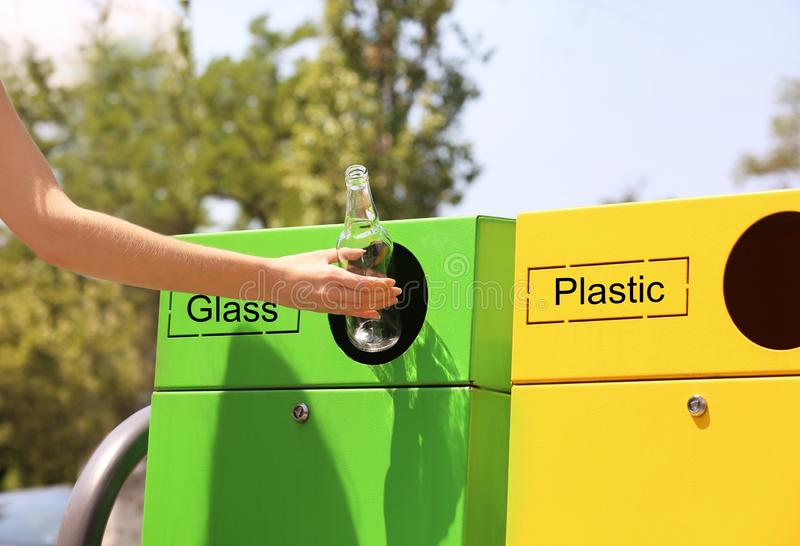 Woman throwing glass bottle into sorting bin on city street, closeup. Recycling. Waste stock image