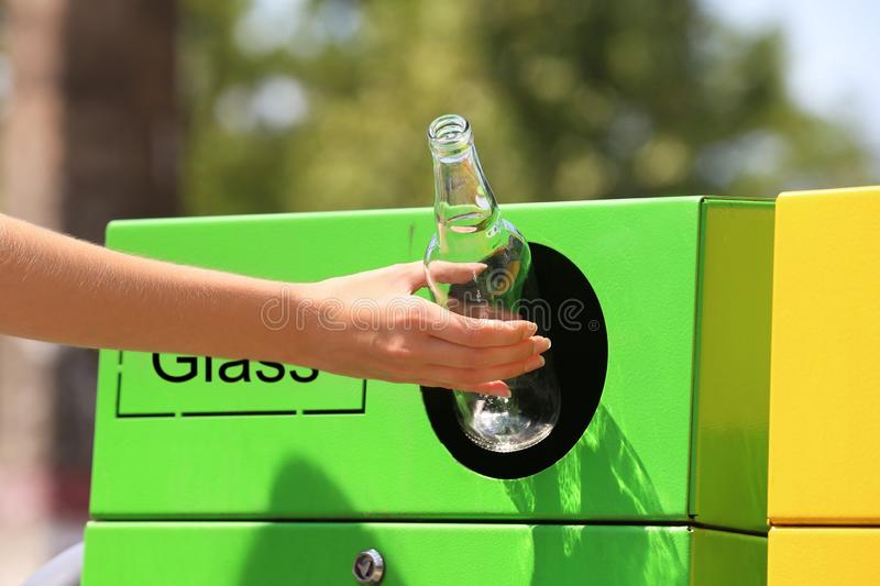 Woman throwing glass bottle into sorting bin on city street, closeup. Recycling waste stock photos