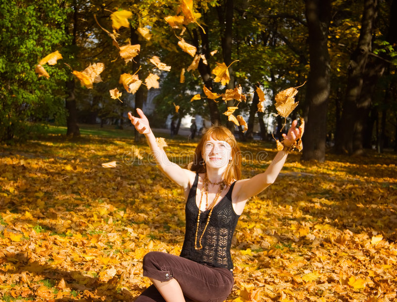 Woman throwing maple leaves stock images