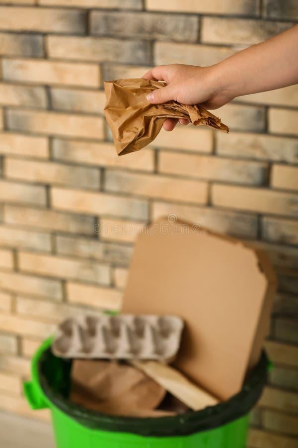 Woman throwing paper bag into garbage bin near brick wall stock photo