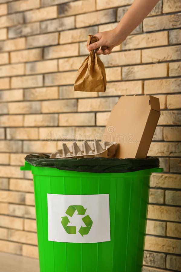 Woman throwing paper bag into garbage bin near brick wall stock images