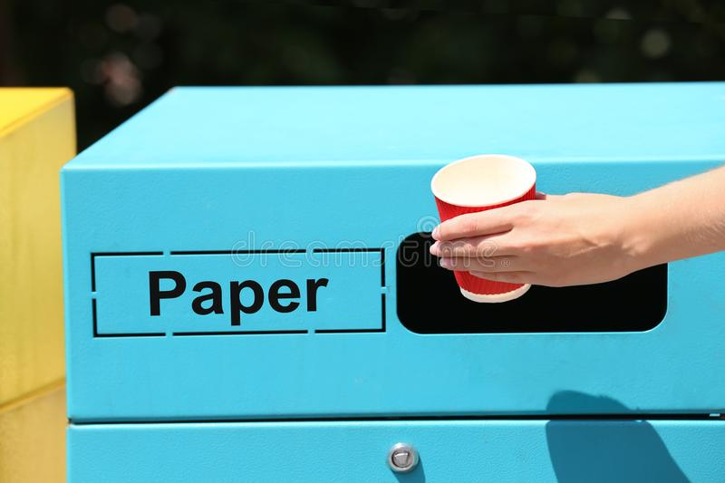 Woman throwing paper cup into sorting bin on city street. Recycling waste. Woman throwing paper cup into sorting bin on city street, closeup. Recycling waste stock image