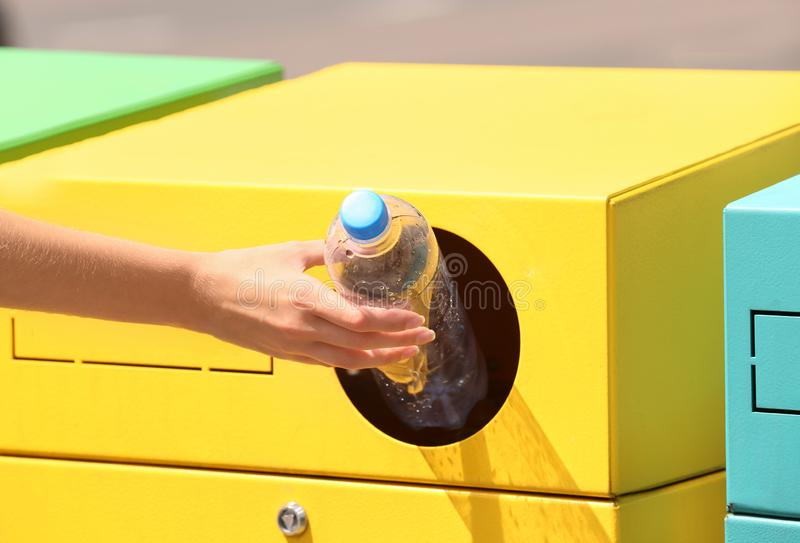 Woman throwing plastic bottle into sorting bin on city street, closeup. Recycling. Waste royalty free stock photo