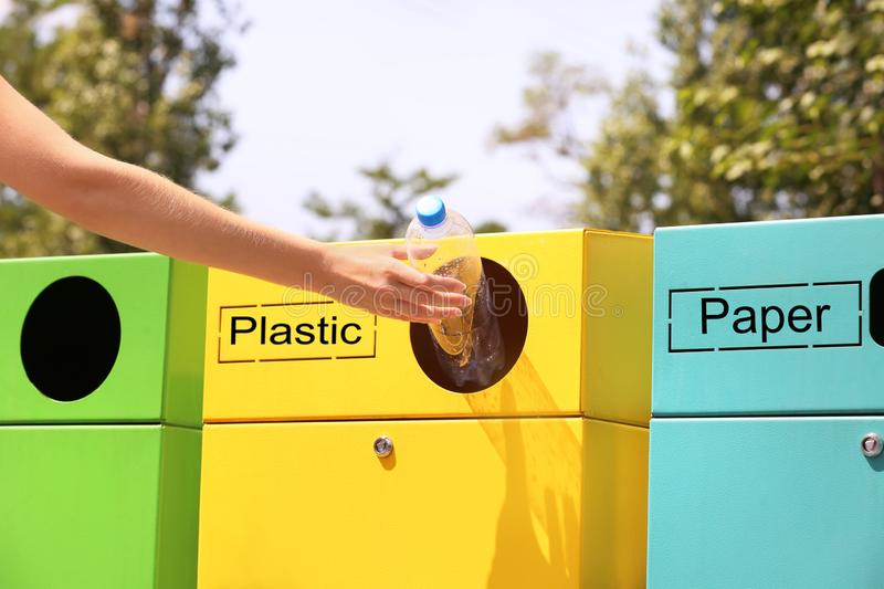 Woman throwing plastic bottle into sorting bin on city street, closeup. Recycling waste royalty free stock photography