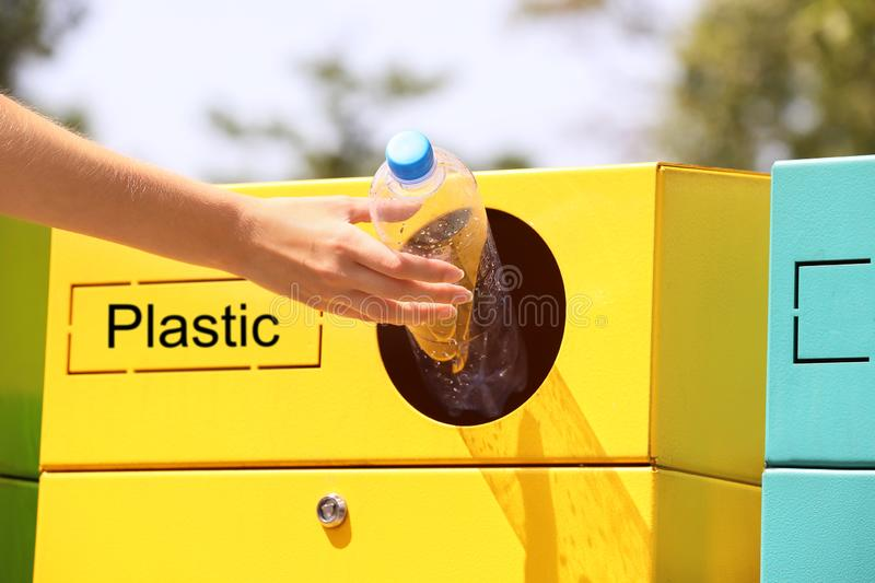 Woman throwing plastic bottle into sorting bin on city street, closeup. Recycling. Waste stock image