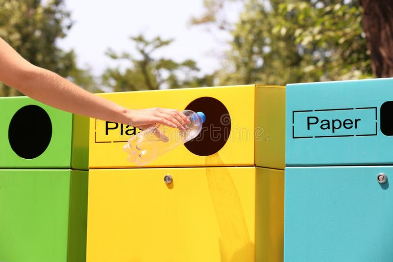 Woman throwing plastic bottle into sorting bin on city street. Recycling waste. Woman throwing plastic bottle into sorting bin on city street, closeup. Recycling royalty free stock photo