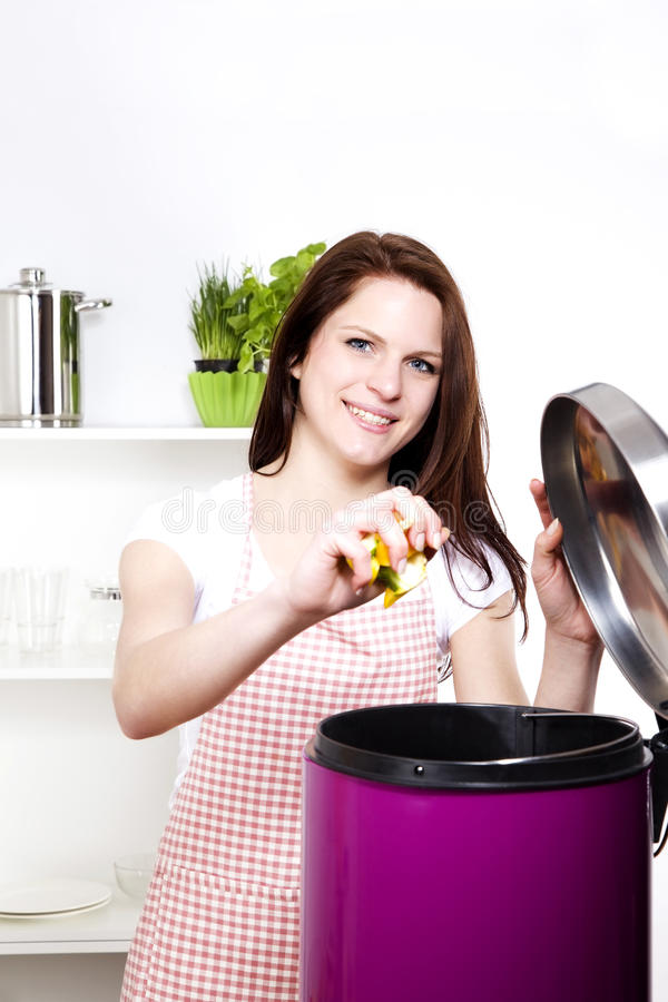 Woman throwing some waste in a trash can. Young smiling woman throwing away some organic waste stock photography