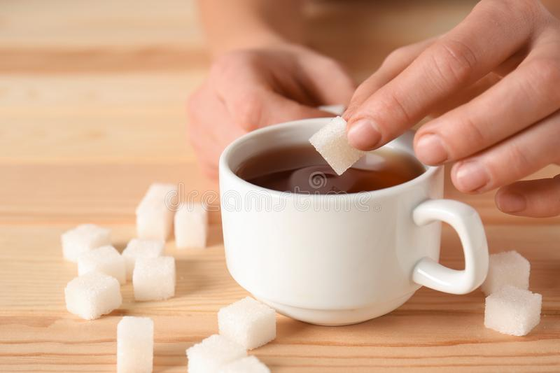 Woman throwing sugar into cup of tea on wooden table, closeup royalty free stock image