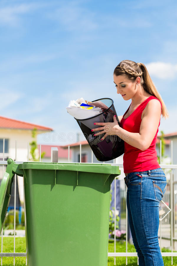Woman throwing waste paper away in container royalty free stock photography