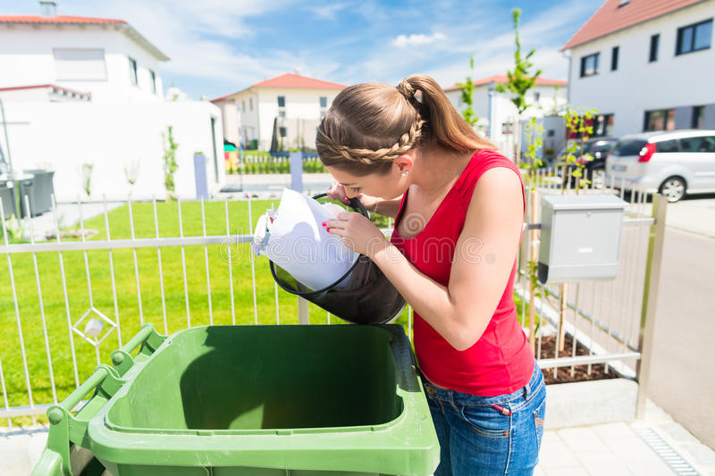 Woman throwing waste paper away in container royalty free stock photo