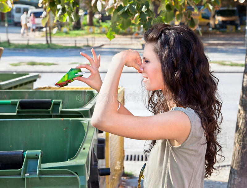 Woman throws garbage in dumpster royalty free stock image