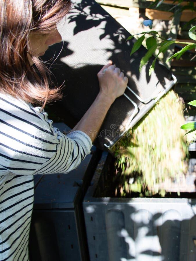 Woman throws organic waste into compost pile stock photos