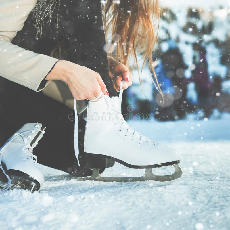 Woman tie shoelaces figure skates at ice rink close-up stock photos
