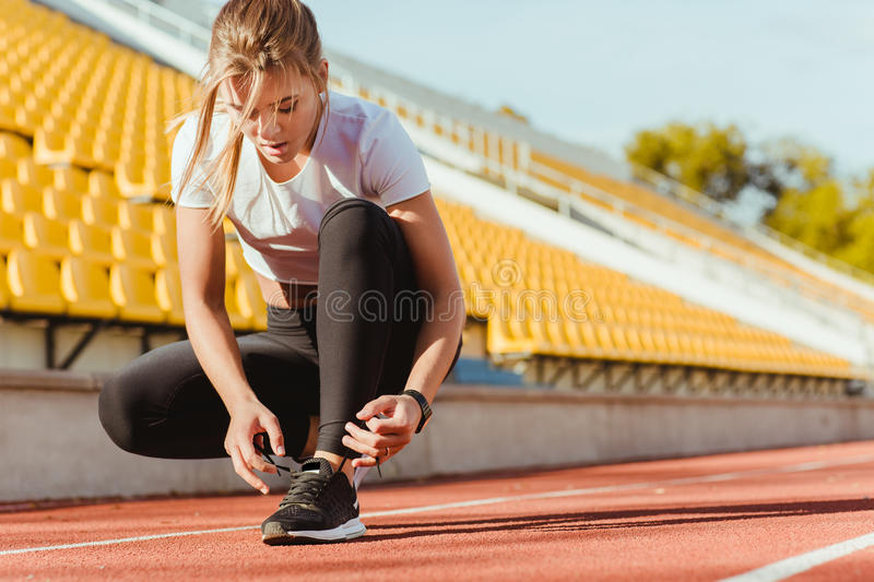 Woman tie shoelaces at outdoor stadium stock images