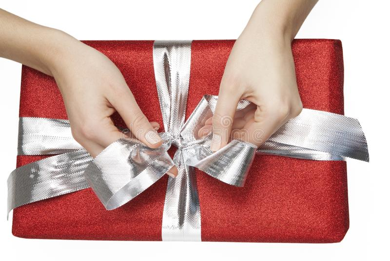 Woman ties a ribbon of a red gift box on white background royalty free stock photo