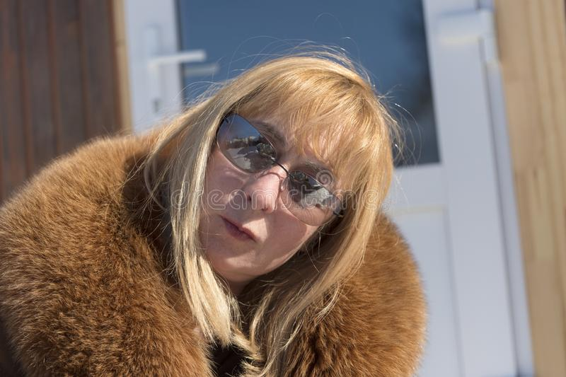Woman With Tilted Head. A woman wearing sunglasses and fur coat posing outdioor with a tilted head stock image
