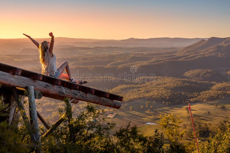 Woman arms outstretched embrace each day. Woman on timber runway pier overlooking beautiful valley. Embrace each day, love life, wellness, lifestyle stock photo