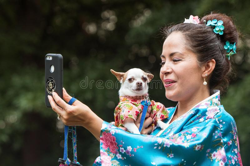 Woman And Tiny Dog Wear Kimonos At Atlanta Doggy Con. Atlanta, GA, USA - August 18, 2018: A woman wearing a kimono takes a selfie as she holds her small dog stock photography