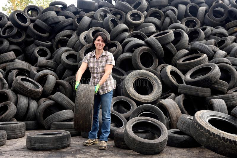 Woman in a tire recycling plant royalty free stock photography