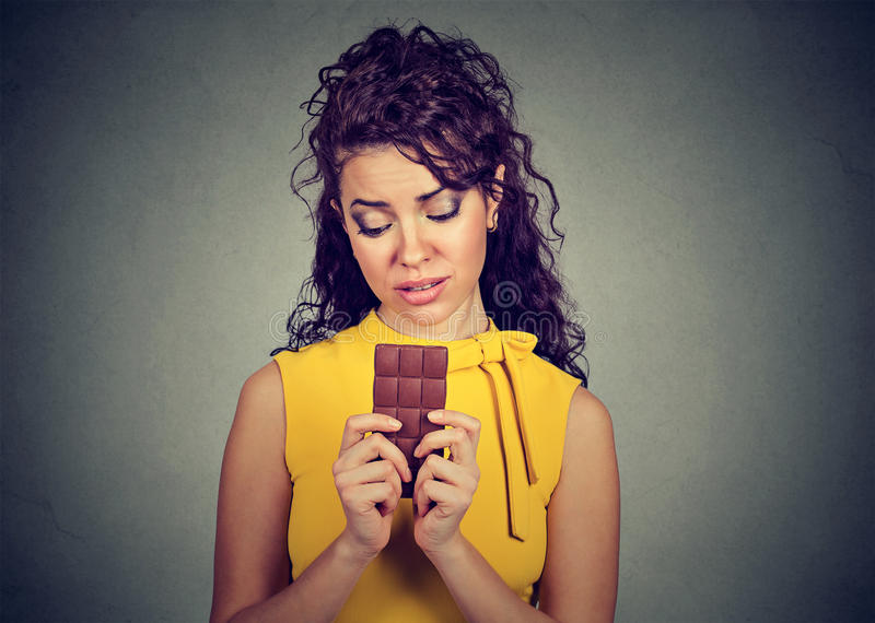 Woman tired of diet restrictions craving sweets chocolate bar royalty free stock image