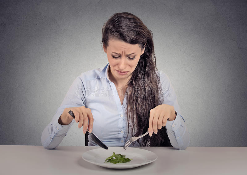 Woman tired of diet restrictions eating green salad stock images