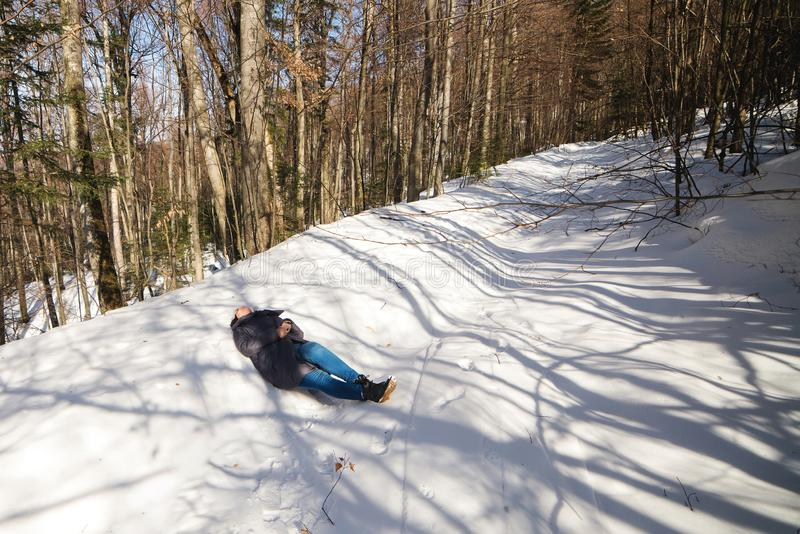 Woman tired of hiking up the hill in winter. Woman lying on a snow in forest stock image