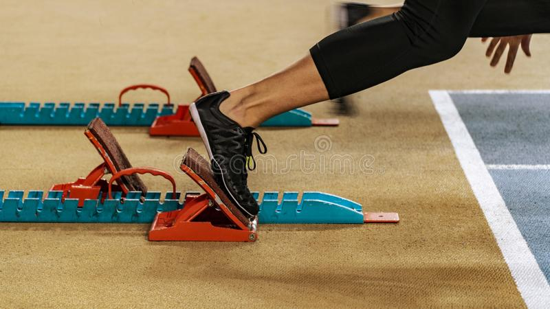 Woman about to start a sprint. Sport. Sprinter leaving starting blocks on the running track. Woman about to start a sprint royalty free stock photo