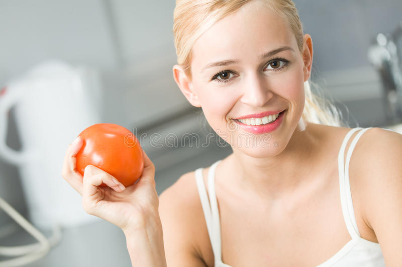 Woman with tomato. At kitchen royalty free stock images