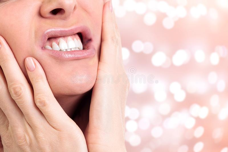 Woman with a toothpain. On an abstract background with blurred lights stock image
