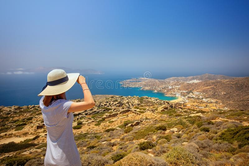 Woman on a top of a hill looking towards a beach, Greece, Cyclades royalty free stock photography