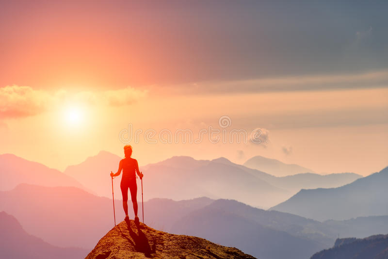 Woman at the top of a mountain. Looking horizon colored stock photography