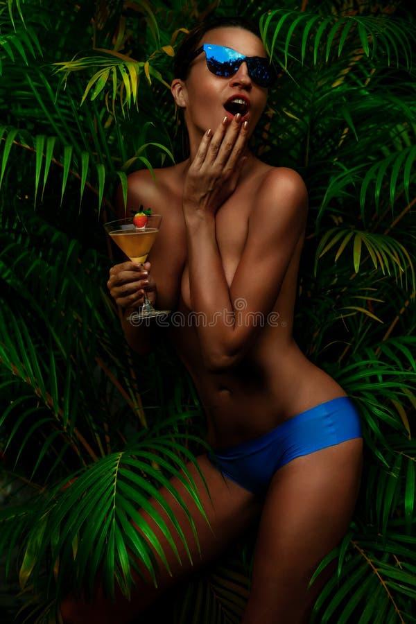 Woman topless drinking martini. Surprised Woman topless drinking martini against palm. Outdoor stock photo