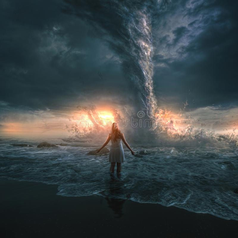 Woman and tornado. A woman bravely stands in front of a large tornado over the ocean stock photo