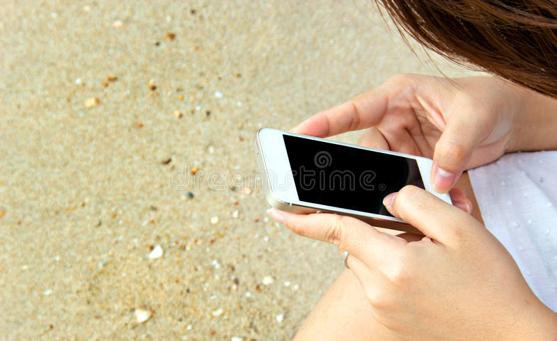 Woman touch screen cell phone on sand. Close up woman finger touch screen cell phone on sand royalty free stock photo