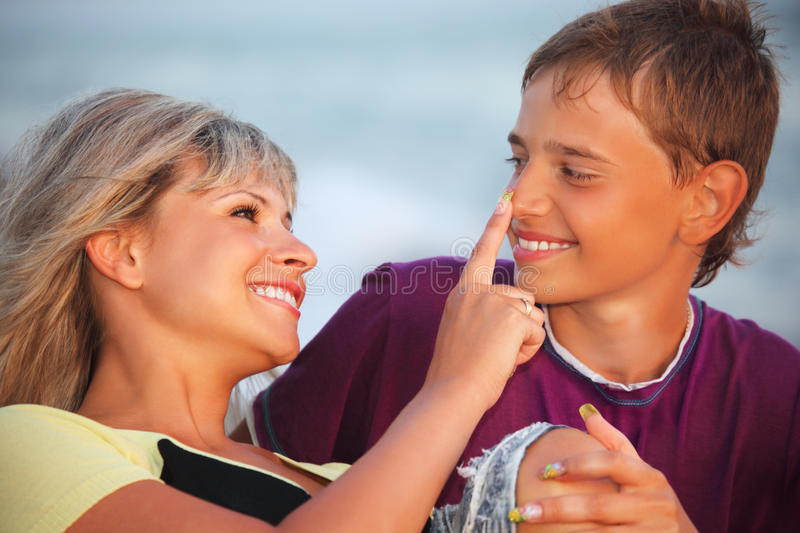 Woman touches with finger nose of smiling boy