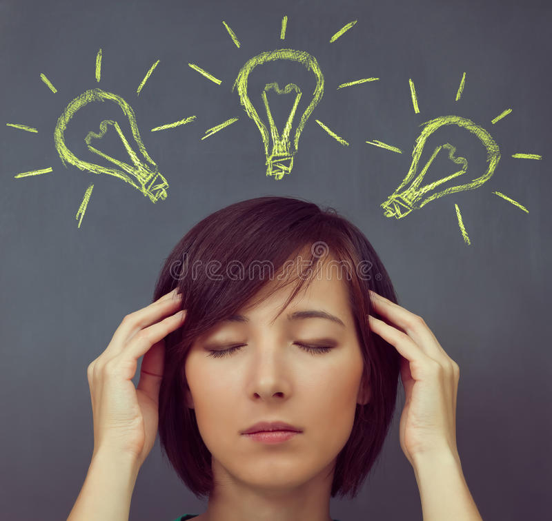 Woman touches her head on a background of light bulbs. Young woman touches her head on a background of light bulbs, concept of new ideas and concentration royalty free stock images