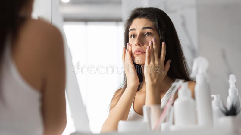 Woman Touching Face Looking At Skin In Mirror At Bathroom stock image