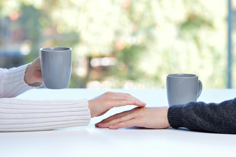 woman touching the hand of her partner during a date in a table of a coffee shop or home royalty free stock images