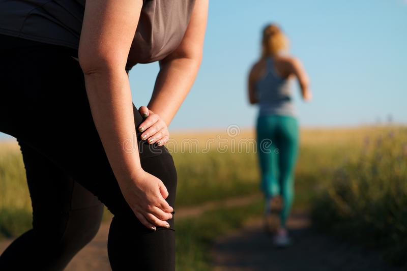 Woman touching her knee, sports injury at jogging stock photo