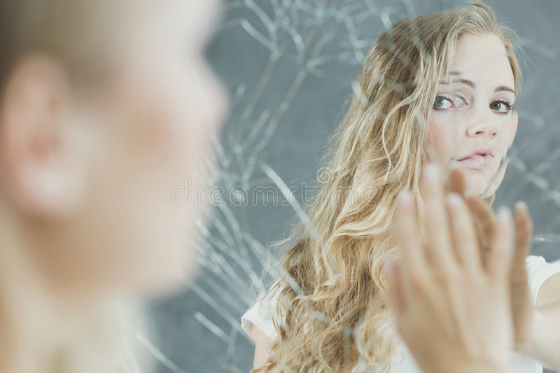 Woman touching her mirror reflection royalty free stock images