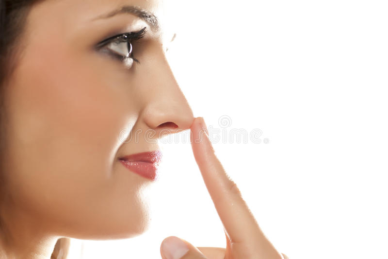 Woman touching her nose. Profile view of a woman touching her nose stock photo