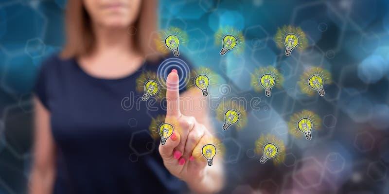 Woman touching light bulbs stock photography