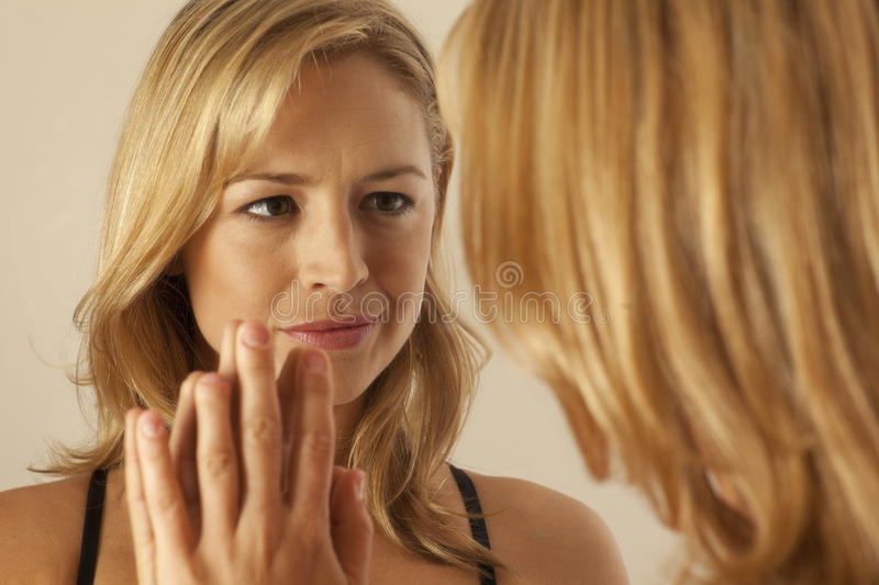 Woman touching mirror while looking at reflection stock photos