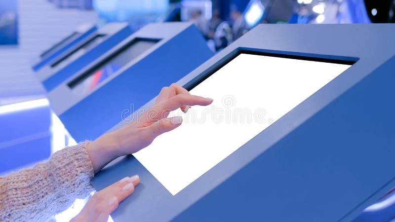 Woman touching white blank display of electronic kiosk - mockup image. Woman hand using white blank interactive touchscreen display of electronic multimedia stock images